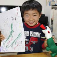 Masaki Gono holds a stuffed green dragon and his drawing that the toy was based on, in Komae, west Tokyo, in November. | KYODO