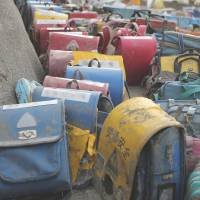 School backpacks and other items found in and around Okawa Elementary School in Ishinomaki are seen March 29, 2011. Many students and staff at the school lost their lives. | SANRIKU KAHOKU SHIMPO CO.