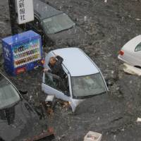A man escapes from his car on March 11, 2011, in Ishinomaki, Miyagi Prefecture. He took shelter in the nearby Ishinomaki Kahoku newspaper building.  | SANRIKU KAHOKU SHIMPO CO.