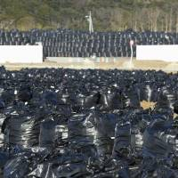 Bags of cesium-tainted soil sit on the ground next to a kindergarten in Futaba, Fukushima Prefecture.   | KYODO