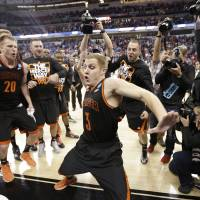 Just bust a move: Mercer guard Kevin Canevari is surrounded by teammates as he dances following the Bears' victory over Duke on Friday in Raleigh, North Carolina. | AP