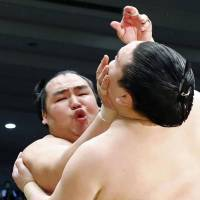 Clear the way: Kakuryu goes on the attack against Hakuho at the Spring Grand Sumo Tournament in Osaka on Saturday. | KYODO