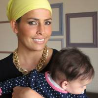 Former Miss World Linor Abargil, who was stabbed, strangled and raped at knife point, poses with her 4-month-old daughter at her home in Netanya, Israel, on March 18. | AP