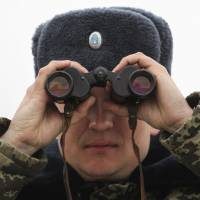 A Ukrainian border guard looks through binoculars at a checkpoint outside the village of Chongar in the Kherson region, adjacent to Crimea, on Wednesday. | REUTERS