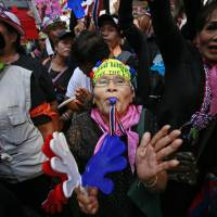Anti-government supporters rally in support of peaceful protests during a memorial for the children killed in recent bomb blasts in Bangkok on Wednesday. | AP