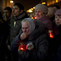 Ukrainians attend Friday's funeral of anti-government protester Bailuk Alexander, 40, killed in a recent clash with riot police in Kiev's Independence Square. | AP