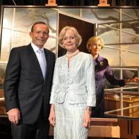 Australian Governor General Quentin Bryce (right) and Prime Minister Tony Abbott pose in front of a painting during a reception at Parliament House in Canberra on Tuesday. Abbott, a staunch monarchist, said up to four knights or dames could be appointed each year, starting with Bryce, the British queen's outgoing representative, and her successor, Peter Cosgrove. | AFP-JIJI