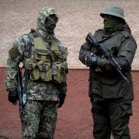 Masked members of the new pro-Russian force, dubbed the 'military forces of the autonomous republic of Crimea,' stand guard in Simferopol, Ukraine, on Monday. | AFP-JIJI