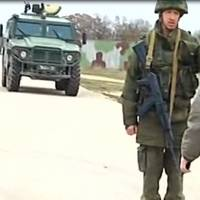 A TV grab taken Tuesday shows Col. Yuli Mamchor (center), commander of a Ukrainian military garrison, approaching Russian forces at Belbek air base near Sevastopol. Russian forces surrounding the air base fired warning shots at Ukrainian servicemen trying to approach. | AFP-JIJI