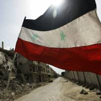A Syrian national flag flutters outside a military barracks in the devastated Baba Amr neighborhood of Homs in May 2012. | AFP-JIJI