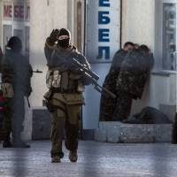 Russian forces arrest Ukrainian Army officers in Simferopol on Tuesday. Russian President Vladimir Putin signed a treaty claiming the Black Sea region of Crimea as Russian territory the same day as Ukraine warned the showdown had entered a 'military stage' with the killing of one of its soldiers on the peninsula. | AFP-JIJI