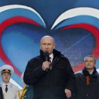 "Russian President Vladimir Putin (center) speaks during a rally and concert called ""We are together"" to support the annexation of Ukraine's Crimea region by Russia. 