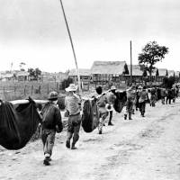 This photo once was thought to have been captured from the Japanese, shows Allied prisoners of war in the Philippines carrying their comrades in slings. In 2009, John E. Love joined a campaign with other Bataan Death March survivors to change the caption of this photo, one of the most famous in the AP library about the march. The photo actually was an Allied POW burial detail. | AP