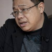 Xiao Yifei, former deputy head of an industrial park in Ningyuan County, describes how he was punched by Communist Party anti-graft investigators in 2012. | AP