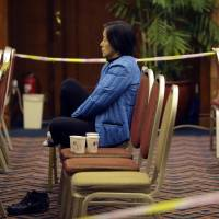 A relative of a passenger aboard Malaysia Airlines Flight MH370 waits at a meeting hall Sunday at Lido Hotel in Beijing. | REUTERS