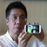 Peter Chong shows a photo of himself with Zaharie Ahmad Shah, the captain of missing Malaysia Airlines Flight MH370, in Sepang, Malaysia, on March 18. | REUTERS
