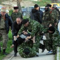 Pro-Russian militiamen beat an unidentified man as Russian soldiers storm a Ukrainian military air base in the Crimean city of Belbek, near Sevastopol, on Saturday. | AFP-JIJI