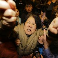A family member of a passenger aboard Malaysia Airlines Flight MH370 shouts at journalists after watching a TV broadcast of a news conference at a Beijing hotel Monday. | REUTERS