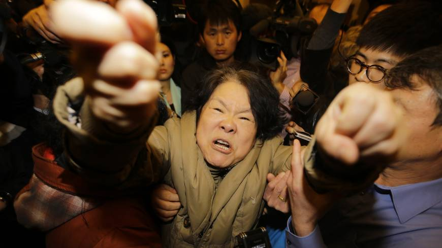 A family member of a passenger aboard Malaysia Airlines Flight MH370 shouts at journalists after watching a TV broadcast of a news conference at a Beijing hotel Monday.