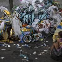 A woman sits next to a pile of discarded costumes after Carnival celebrations at the Sambadrome in Rio de Janeiro on Tuesday. | AP