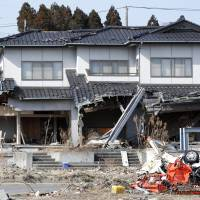 A man looks at a house Saturday in Minamisoma, Fukushima Prefecture, that was damaged by the tsunami following the Great East Japan Earthquake of March 11, 2011. | BLOOMBERG