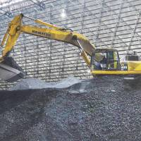An excavator built by Komatsu Ltd. scoops up coal inside a coal storage yard at the Nakoso power station run by Joban Joint Power Co. in Iwaki, Fukushima Prefecture, last month. | BLOOMBERG