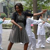 U.S. first lady Michelle Obama performs tai chi with students at a high school in Chengdu, southwest China, on Tuesday. Obama, who arrived in the country last Thursday, is focusing on education and cultural exchanges during her tour. | AFP-JIJI