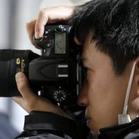 A man tries out a Nikon D600 digital camera at the CP+ Camera and Photo Imaging Show in Yokohama last year. | BLOOMBERG