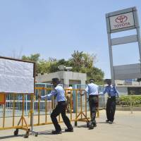 Security guards move a barricade outside a closed plant of Toyota Motor Corp.'s India unit near Bangalore last week. The carmaker said it has partially resumed operations with the help of nonunion workers after union members walked out over pay disputes. | REUTERS
