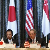Akira Amari, the minister in charge of TPP talks, attends a news conference with U.S. Trade Representative Michael Froman following a February meeting in Singapore of trade ministers from the states negotiating the free trade pact. | KYODO