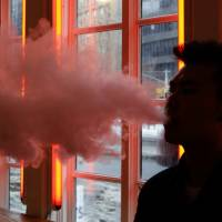 A patron exhales vapor from an e-cigarette at The Henley Vaporium in New York on Feb. 20, at one of a growing number of establishments pushing e-cigarettes and related products. | AP