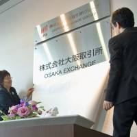 A sign for Osaka Exchange Inc., the new name of the former Osaka Securities Exchange Co., is unveiled in Osaka's Chuo Ward on Monday, the same day when the Tokyo and Osaka stock exchanges integrated the trading of derivatives operations into the Osaka bourse. | KYODO