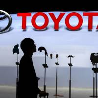 A journalist looks at Toyota Motor Corp.'s booth during media day at the Geneva Motor Show on Tuesday. | AFP-JIJI