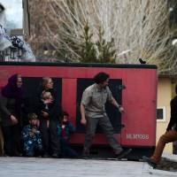 Foreigners take refuge behind a generator after they were evacuated from an American charity that came under attack by Taliban gunmen Friday in Kabul. The assault by militants was one of a spate that have hit the Afghan capital in recent weeks. | AFP-JIJI