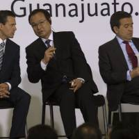Forging strong ties: Mexican President Enrique Pena Nieto, left, speaks with Honda CEO Takanobu Ito, center, as Ildefonso Guajardo, Mexico's economy minister, checks paperwork at the opening ceremony for Honda Motor Co.'s new plant in Celaya, Mexico, on Feb. 21. | BLOOMBERG