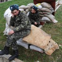Ukrainian Air Force pilots sit on sandbags at the Belbek air base near Sevastopol the same day. | AFP-JIJI
