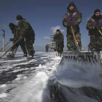 Decontamination time: U.S. Navy crews mop up the flight deck to remove radioactive substances from USS Ronald Reagan on March 23, 2011, off the coast of Tohoku, after the aircraft carrier's forces spent 10 days helping with rescue and aid missions in the wake of the 3/11 earthquake and tsunami. | AP