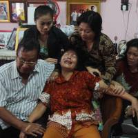 Risman Siregar (left) comforts his wife, Erlina Panjaitan in Medan on Sunday. They are the parents of Firman Chandra Siregar, a 24-year-old passenger of Malaysia Airlines Flight 370, which went missing on Saturday. | AFP-JIJI