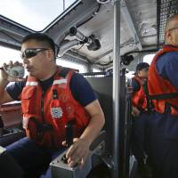 Coast Guard officer William Pless communicates on the radio while steering a Coast Guard vessel during a drug patrol off the San Diego coast. Smugglers have been increasingly using large vessels to carry multi-ton loads of cocaine and marijuana hundreds of miles offshore. | AP