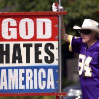 The Rev. Fred Phelps Sr. is seen displaying one of his infamous protest signs in this file photo. The fiery founder of the Westboro Baptist Church in Kansas has died at the age of 84, his family said Thursday. | AP