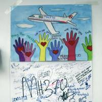 Paintings for passengers aboard a missing Malaysia Airlines plane are pasted on a wall at a viewing gallery at Kuala Lumpur International Airport in Sepang, Malaysia, on Tuesday. | AP