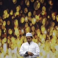 A Muslim prayer is performed for passengers of missing Malaysia Airlines Flight MH370 at the departure hall of Kuala Lumpur International Airport on Thursday. | REUTERS