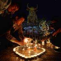 Chinese mourners light candles at the scene of the terrorist attack at the main train station in Kunming, Yunnan province, on Sunday. | AFP-JIJI