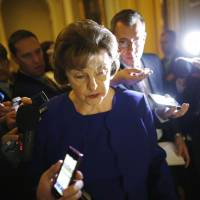 U.S. Sen. Dianne Feinstein is trailed by reporters as she walks to the weekly Democratic caucus policy luncheon at the U.S. Capitol in Washington on Tuesday. A dispute between the CIA and a U.S. Senate committee that oversees it burst into the open earlier the same day when Feinstein accused the agency of spying on Congress and possibly breaking the law. | REUTERS