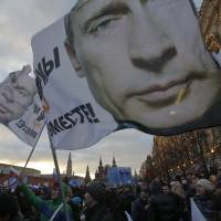 People wave flags with images of Russian President Vladimir Putin emblazoned on them during a rally in support the Russia's annexation of Ukraine's Crimea region in Moscow's Red Square on Tuesday. | REUTERS