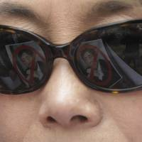 Defaced portraits of Prime Minister Shinzo Abe are reflected in a protester's sunglasses during a rally outside the Japanese Embassy in Seoul on Saturday.  | AP