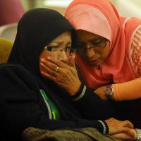 Family members of passengers aboard a missing Malaysia Airlines plane are seen crying at a hotel in Putrajaya, Malaysia, on Sunday. | AP