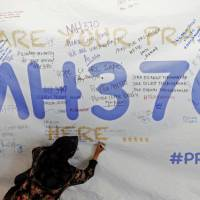 A woman writes a message of hope for the passengers of missing Malaysia Airlines Flight MH370 on a banner at Kuala Lumpur International Airport on Wednesday. | REUTERS