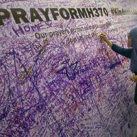 A Malaysian woman leaves a message for passengers aboard a missing Malaysia Airlines plane, at a shopping mall in Petaling Jaya, near Kuala Lumpur on Sunday. | AP