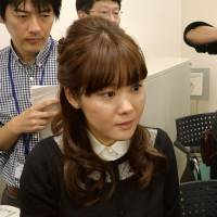 Biologist Haruko Obokata (center) of the Riken institute, is surrounded by reporters in Kobe in January after announcing the discovery of a new method of producing stem cells. The study is attracting scrutiny for alleged irregularities. | KYODO